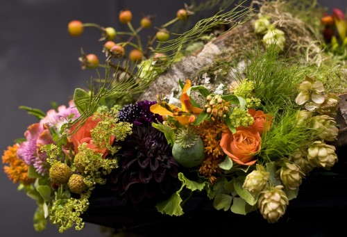 woodland arrangement on wooden disks with dahlias, texture and poppy pods, Fra