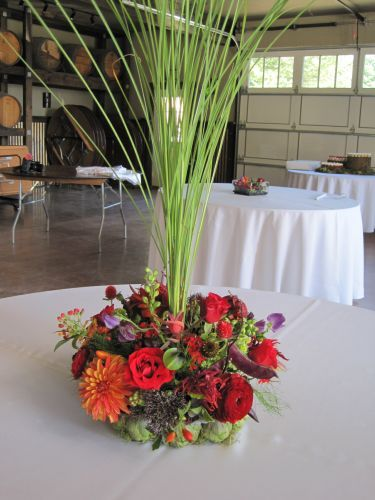 bright orange and red centerpiece with tall grass in artichoke container, George Crest, Françoise Weeks