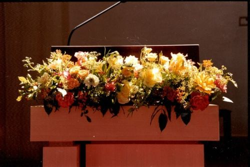 lectern decorated with yellow and peach flower garland,Françoise Weeks