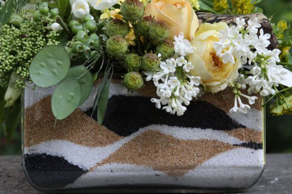 pale yellow, white and green arrangement in container filled with colored sand, Françoise Weeks